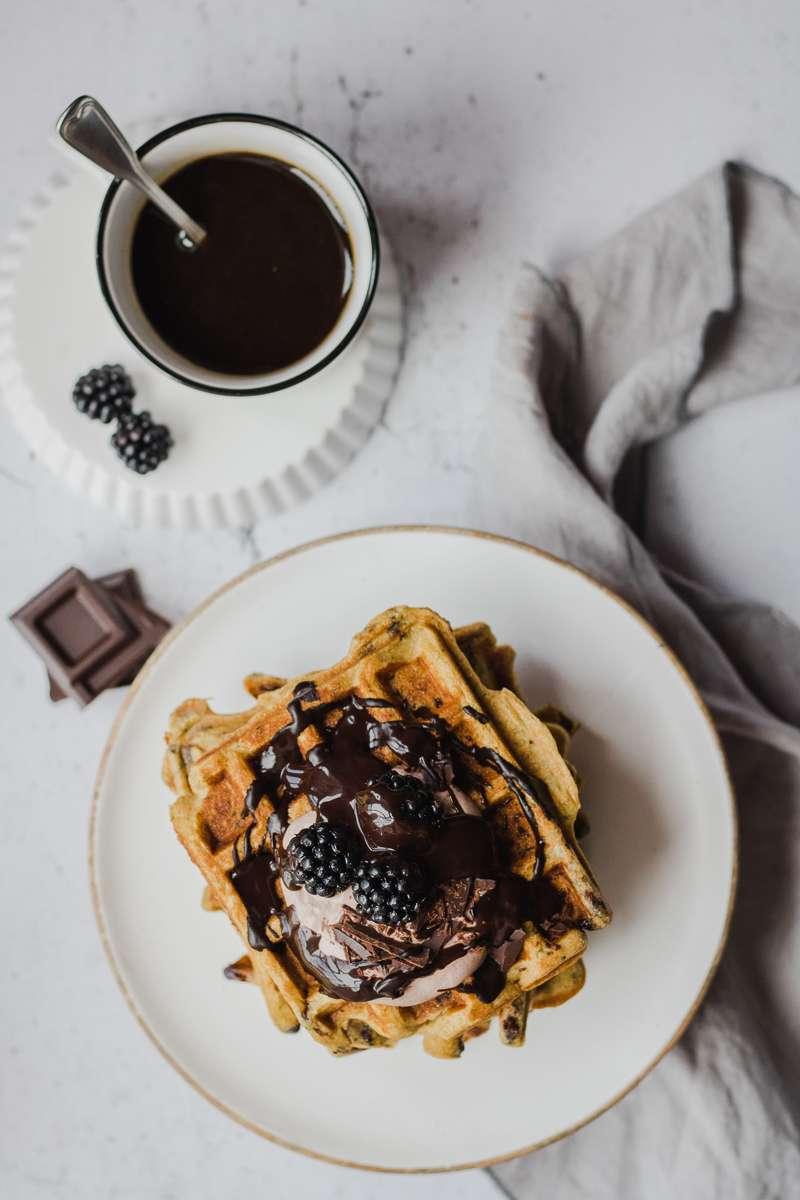 Pila di waffle di zucchine iperproteici al cioccolato con more