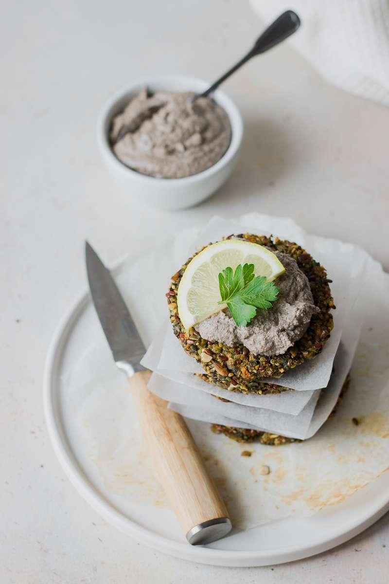 Pila di veg burger di quinoa, patata dolce, fave con salsa tofu e olive