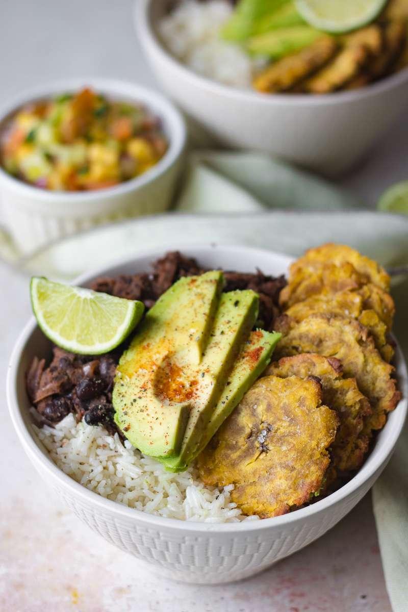 Bowl cubana vegana con avocado, fagioli neri, salsa al mango e tostones al forno