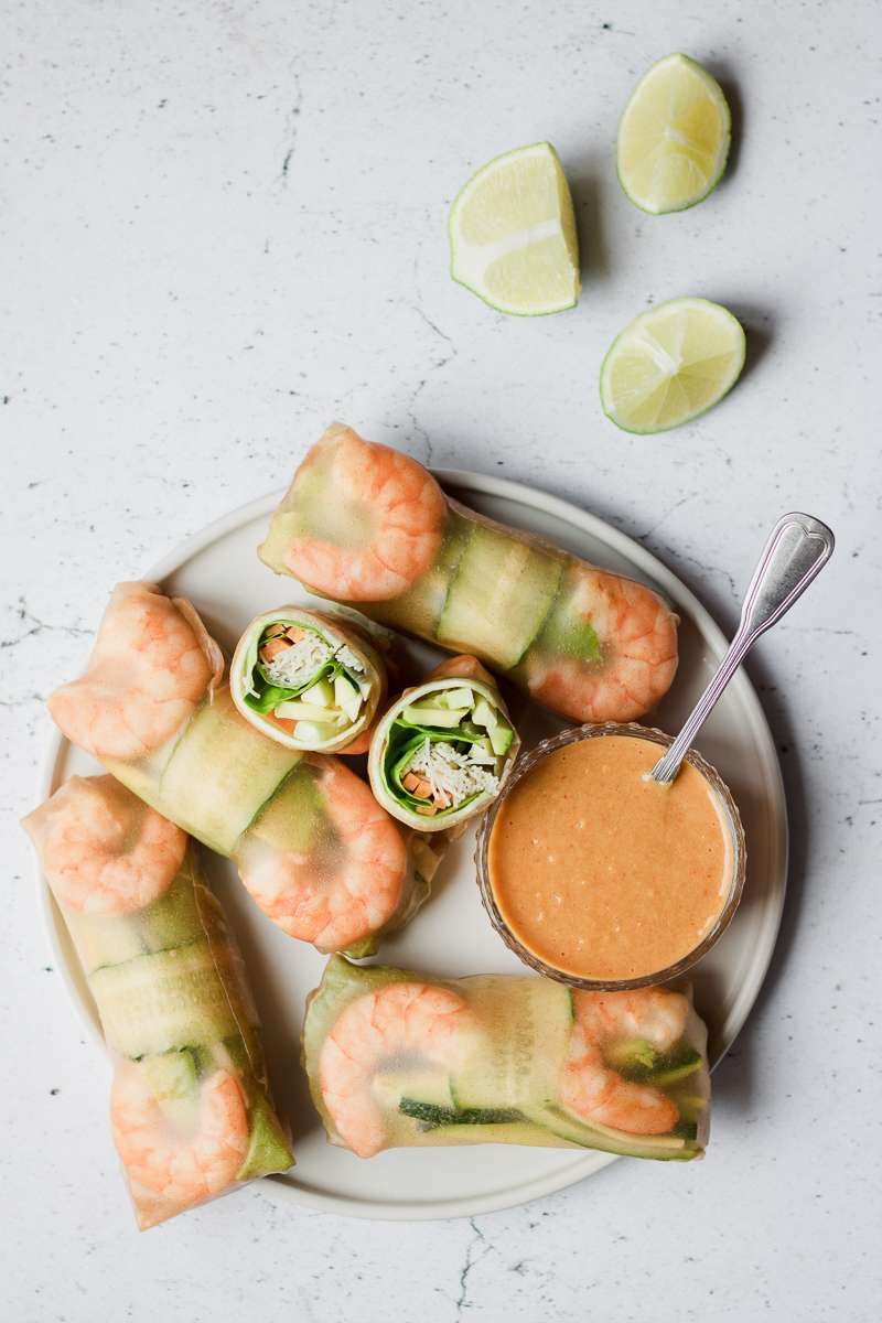 piatto di involtini vietnamiti di carta di riso integrale, con gamberi e verdura e salsa al burro di arachidi e mango, senza glutine e senza latticini
