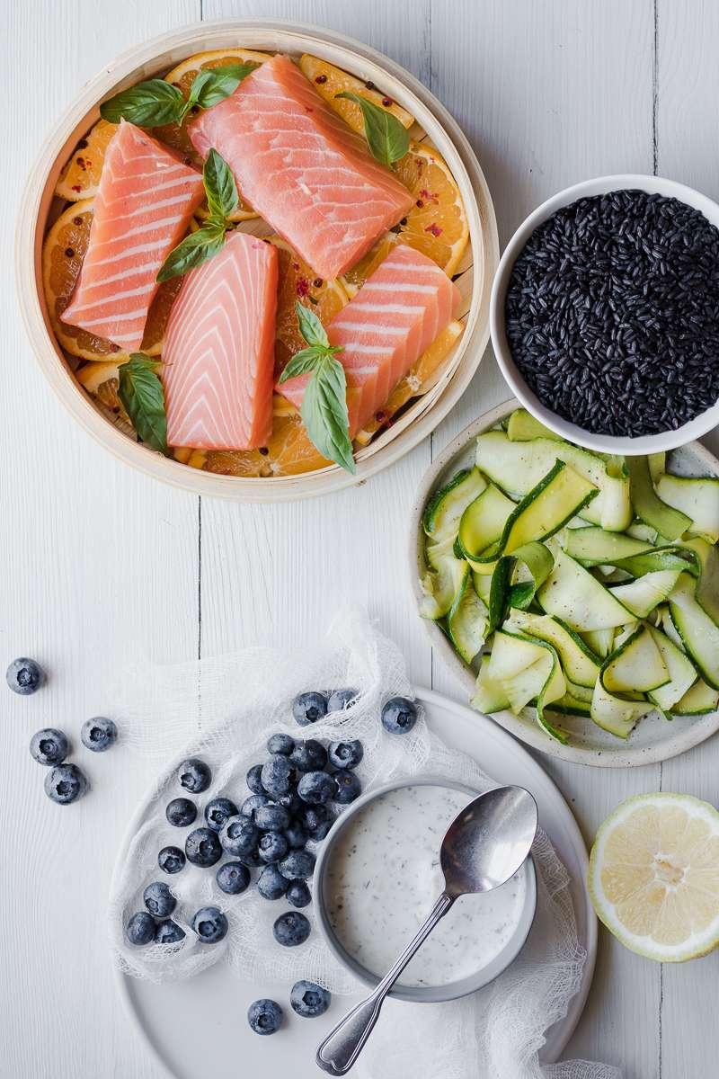 Ingredienti per l'insalata di riso nero, salmone al vapore, zucchine marinate e mirtilli