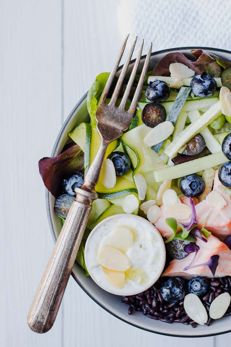 Ciotola di insalata di riso nero con salmone al vapore, zucchine marinate e mirtilli