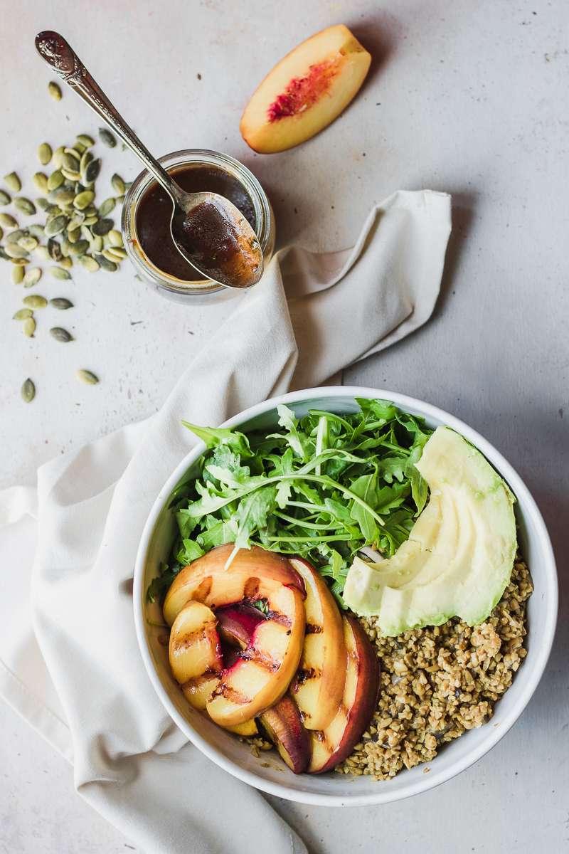 Ingredienti dell'insalata di bulgur di soia, pesche grigliate, rucola e vinaigrette