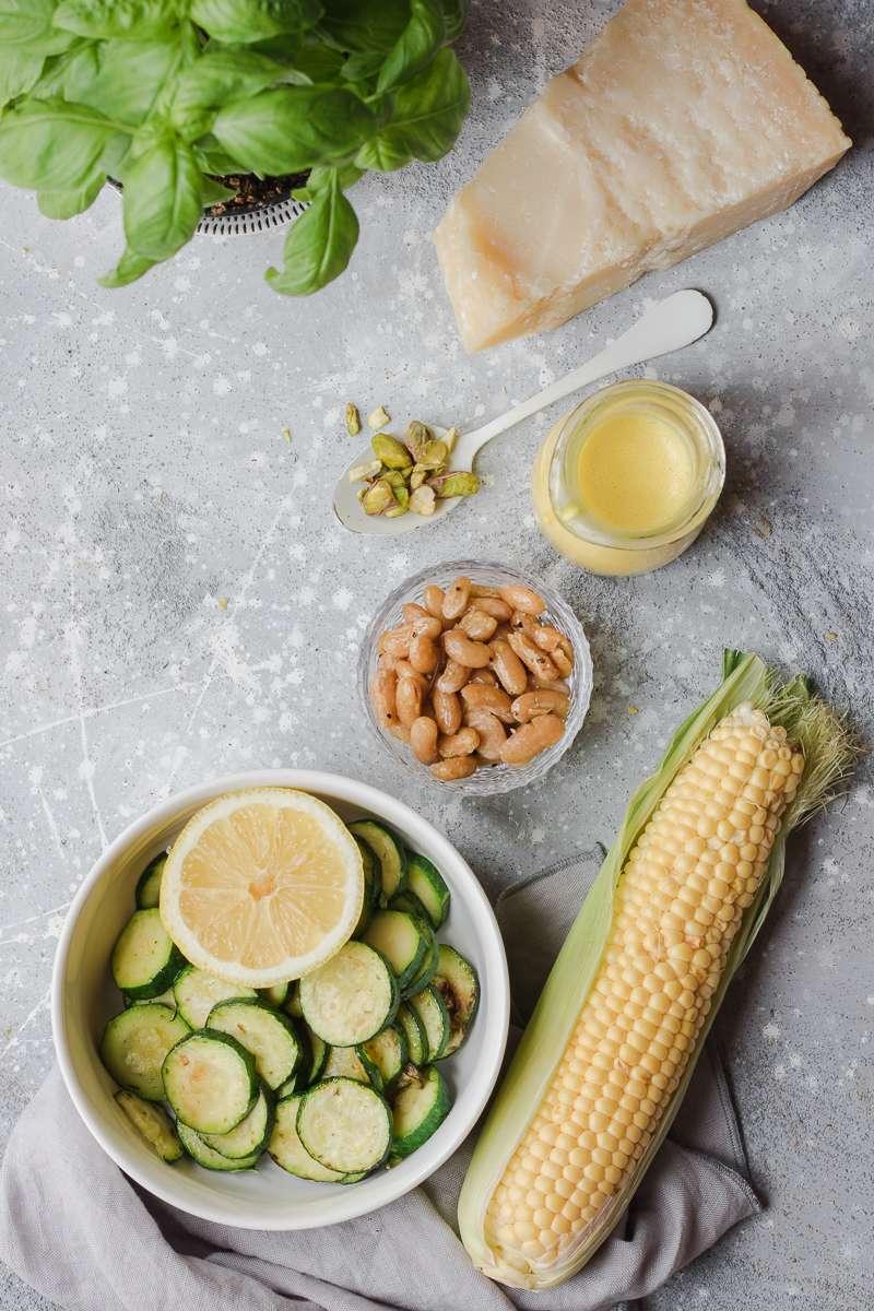 Ingredienti per insalata di zucchine e mais, con cannellini, parmigiano, pistacchi e salsa allo zafferano