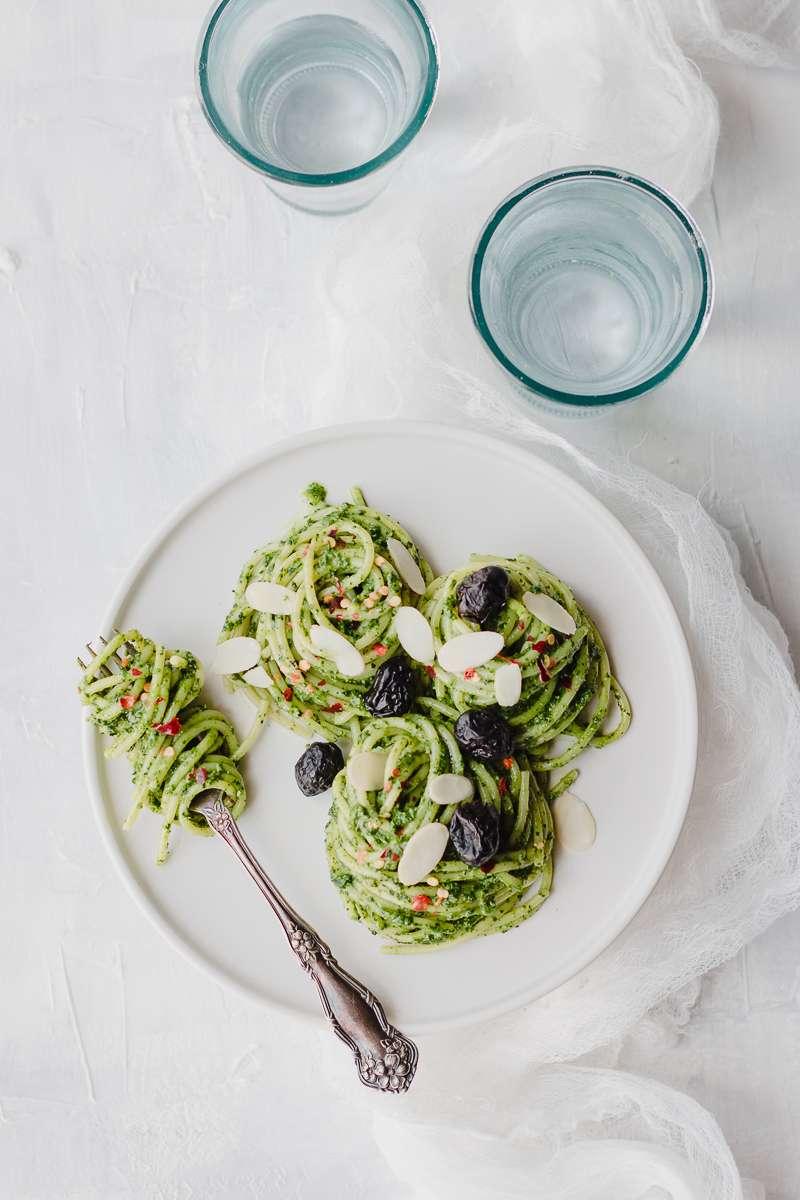 Piatto di spaghetti al pesto di cavolo nero e riccio con olive